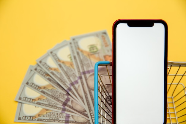 Smartphone, metal market basket and banknotes of dollars on yellow background. concept of online shopping from home.