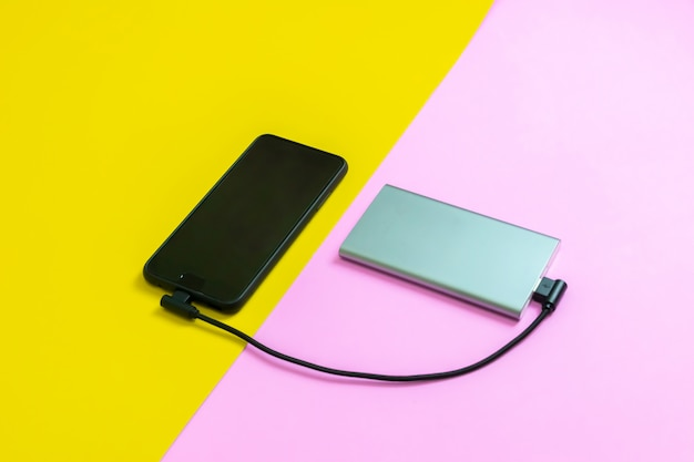 Smartphone mobile phones charging batteries by power bank pink and yellow background
