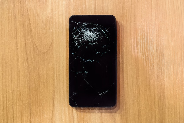 깨진 화면이 있는 스마트폰 모바일. 배경 나무