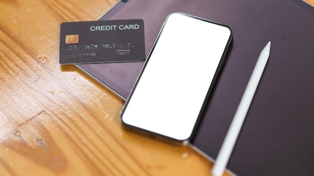 스마트폰은 나무 테이블 온라인 결제 개념에 신용 카드가 있는 빈 화면을 조롱합니다.