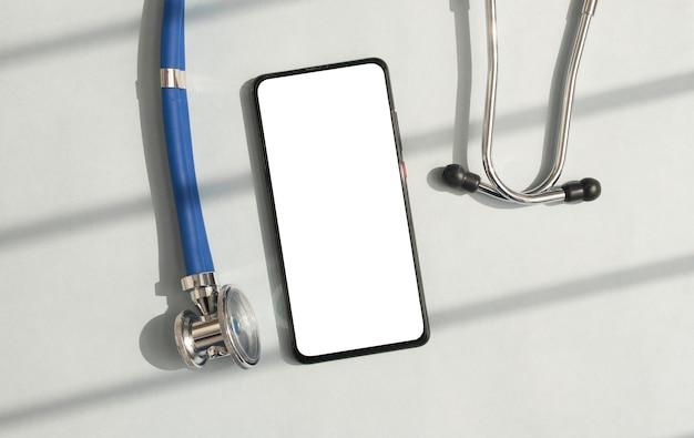 스마트폰은 건강 관리 애플리케이션을 위한 스마트폰과 청진기의 흰색 빈 화면을 조롱합니다.