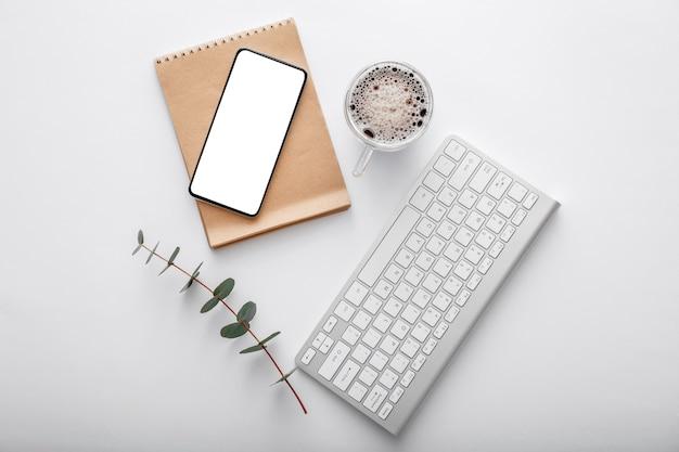스마트폰은 흰색 작업 공간 책상에 메모 키보드 커피 컵 녹색 식물로 조롱합니다. 평면도 평면도. 현대 사무실 책상 작업 공간에 휴대 전화입니다.