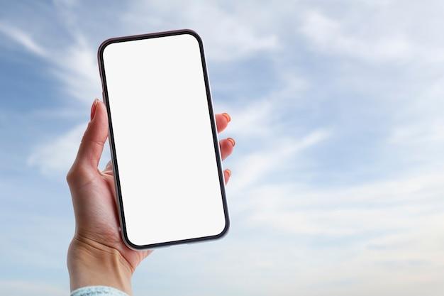 スマートフォンのモックアップ。雲のある美しい空を背景にスマートフォンを手に持つ女性。