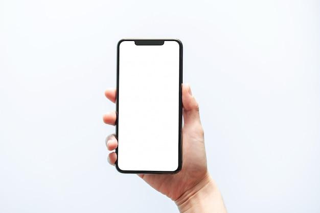 스마트 폰 모형. 손을 잡고 검은 전화 흰색 화면을 닫습니다. 흰 배경에 고립. 휴대 전화 프레임리스 디자인 컨셉입니다.