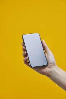 Smartphone mockup. female hand holding black cellphone with with blank display on yellow background