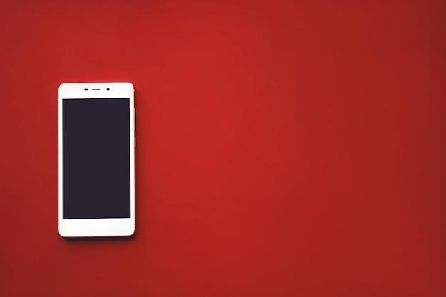 빨간색 배경에 스마트폰 모형입니다. 복사 공간에 텍스트를 입력하려면 평면도 상위 뷰입니다.