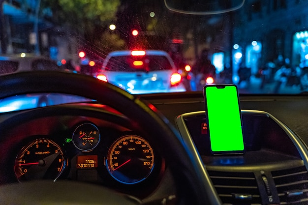 Smartphone mockup with green screen in the car while driving to add gps or app