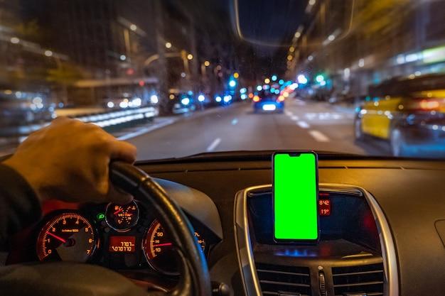 Gps 또는 앱을 추가하기 위해 운전하는 동안 자동차에 녹색 화면이 있는 스마트폰 모형
