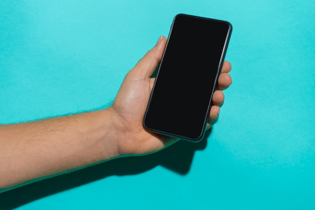 화려한 파란색 배경 복사 공간 앞에서 전화를 들고 있는 남자 손으로 스마트폰 모형
