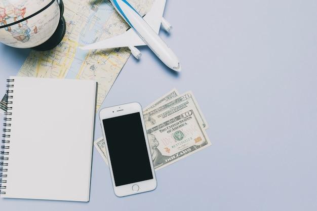 Smartphone and money near tourist stuff