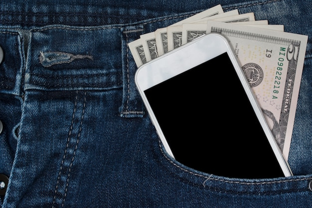 Smartphone and money in pocket jeans.