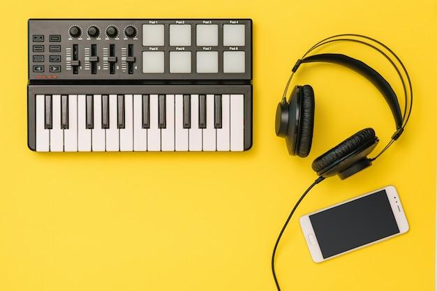 明るい黄色の背景にスマートフォン、ミュージックミキサー、ヘッドフォン。職場組織の概念。録音、通信、音楽鑑賞のための機器。