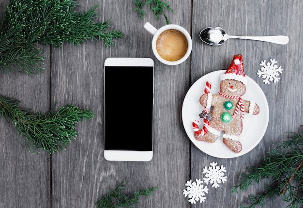 Smartphone near biscuit snowman on plate near cup of drink, snowflakes and twigs