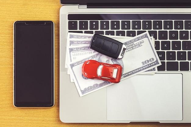 Смартфон возле модели автомобиля, денег и ноутбука на деревянном столе. покупки в интернете и оплата автомобиля с помощью ноутбука