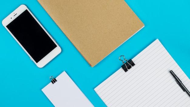 Смартфон возле коробки и бумаги с зажимами Бесплатные Фотографии