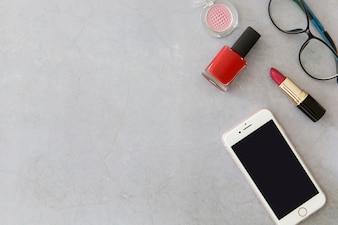 Smartphone near cosmetics and glasses