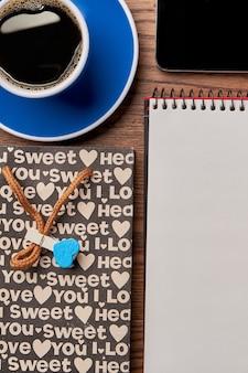 一杯のコーヒーの近くのスマートフォン。ノートと紙袋。コーヒーブレイクを取ります。