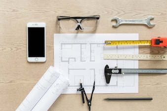 Smartphone near drafts and construction supplies