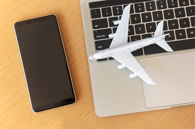 ノートパソコンの近くのスマートフォンとテーブルの上の飛行機