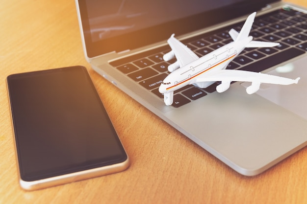 Smartphone near laptop computer and airplane on table. online ticket booking concept