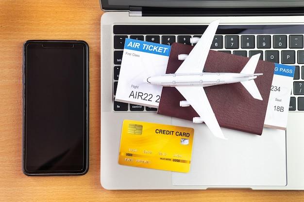 ラップトップコンピューターの近くのスマートフォンとテーブルの上の飛行機。オンラインチケット予約のコンセプト