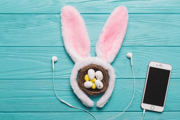 Smartphone near neast and bunny ears