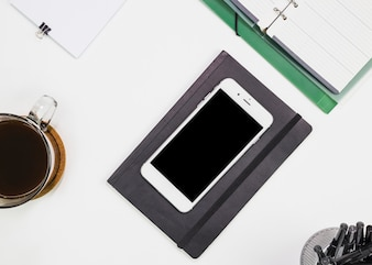 Smartphone near notebook and cup of drink