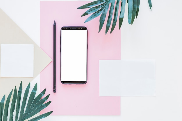 Smartphone near papers and palm trees on white desk