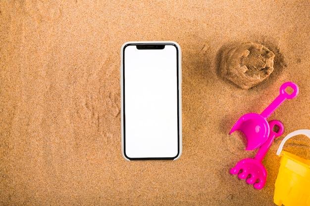 Smartphone vicino al set di giochi di sabbia