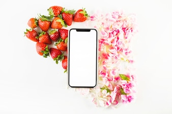 Smartphone near strawberries and petals
