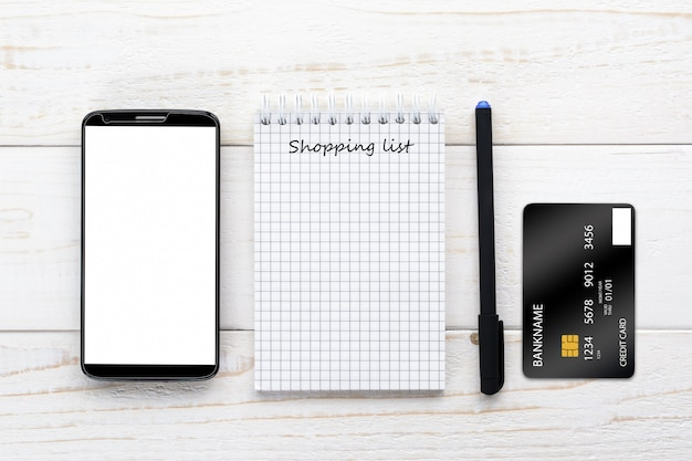 Smartphone, notebook and credit card on a white table