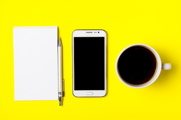 Smartphone, notepad and cup of coffee on a yellow background