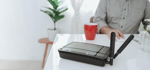 Крупный план беспроводного маршрутизатора и человека используя smartphone на ofiice живущей комнаты дома.