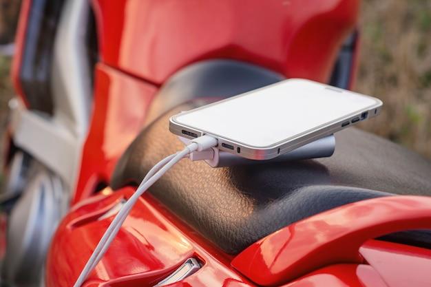 오토바이와 파워 뱅크의 스마트폰은 자연을 배경으로 휴대폰을 충전합니다.