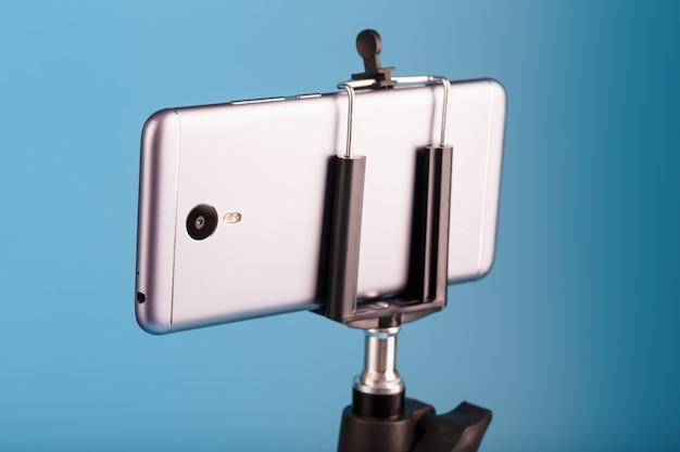 青い背景の写真ビデオカメラとしての三脚のスマートフォン。ブログのビデオと写真を記録します。