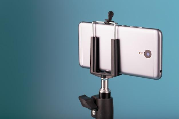 Смартфон на штатив, как фото-видео камера на синем фоне. запишите видео и фото для вашего блога.