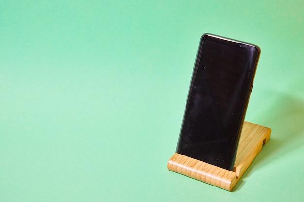 녹색 배경에 나무 스탠드에 스마트폰