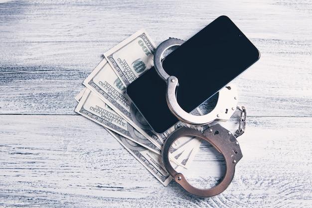 Смартфон на банкнотах с наручниками