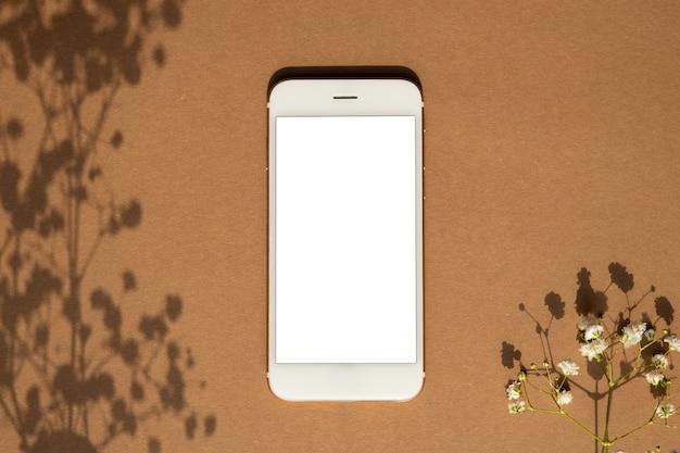 茶色のパステルカラーの背景にスマートフォン。携帯電話ゲームデザイン、モバイルアプリケーション、壁紙、ウェブサイトのモックアップ。植物と影の上面図
