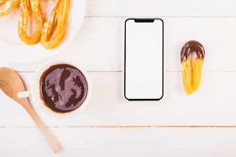 Smartphone on kitchen table with dessert