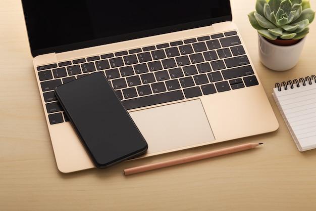 木製のテーブル上のラップトップ上のスマートフォン
