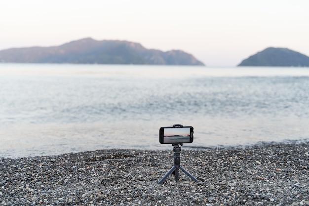 一脚スティック上のスマートフォン。海の夕日のビデオを記録。コンテンツクリエータ