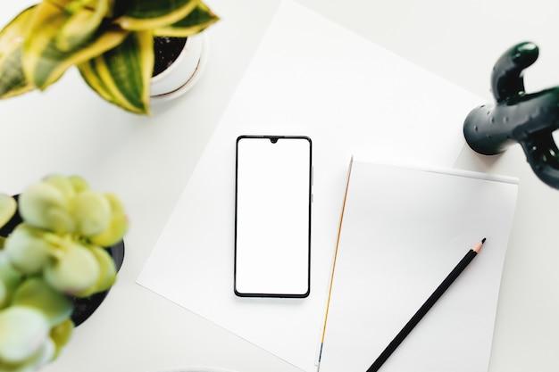 흰색 테이블에 스마트 폰, 가정, 사무실 물건에서 작동합니다. 고품질 사진