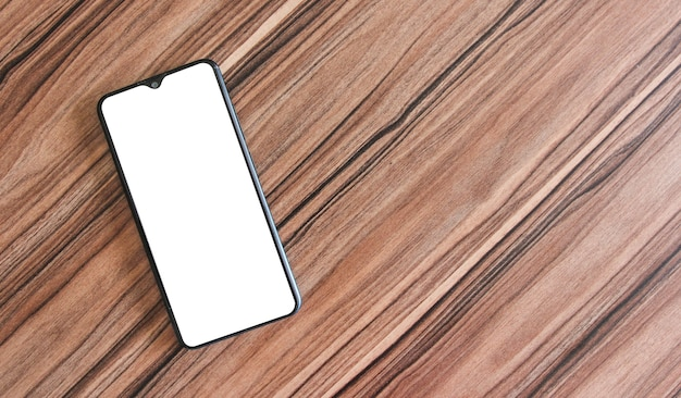 Смартфон на деревянных фоне. макет с изолированным пустым экраном для использования в собственном мобильном приложении. вид сверху.