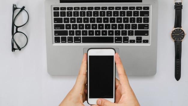 Смартфон над ноутбуком, планшетным пером, очками и часами на белом фоне пустого пространства