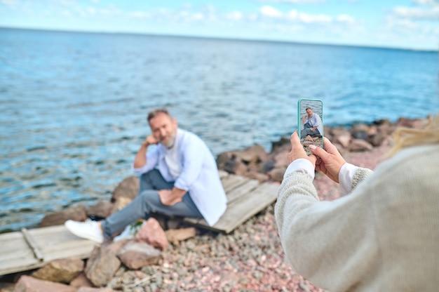 Смартфон, фото. женские руки со смартфоном, фотографирующим человека, сидящего и позирующего на берегу моря в погожий день