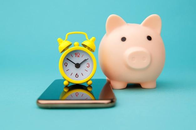Смартфон, розовая копилка и будильник на синем.