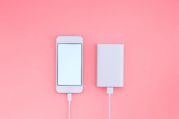 Smartphone and powerbank on pink background. powerbank charges the phone against the wall. flat lay.