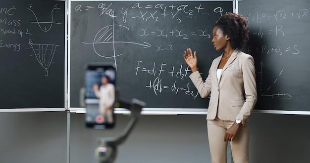 学校でのスマートフォン録画ビデオレッスン。オンライン学習。クラスで数学や物理の公式を説明するアフリカ系アメリカ人の若い女性教師。検疫の概念。インターネットで勉強する。隔離。
