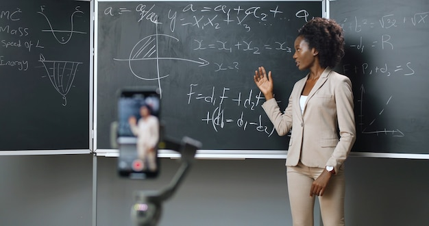 Smartphone recording video lesson at school. online studying. african american young female teacher explaining math or physics formulas at class. quarantine concept. study by internet. isolation.